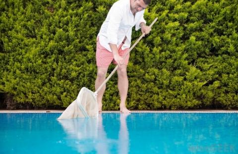 Man removing debris from pool